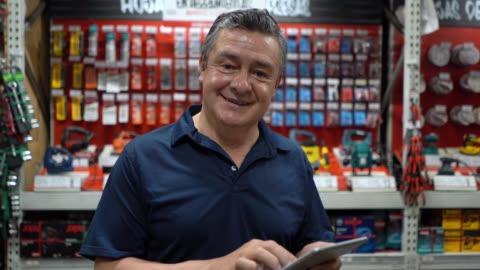 vídeos y material grabado en eventos de stock de vendedor maduro latinoamericano mirando la tableta y luego la cámara sonriendo en una ferretería - work tool