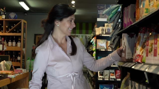 stockvideo's en b-roll-footage met latijns-amerikaanse volwassen vrouw boodschappen bij de supermarkt producten toe te voegen aan haar mandje - dairy product