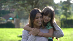 Latin american mother and daughter at the park hugging each other while looking at camera very happy