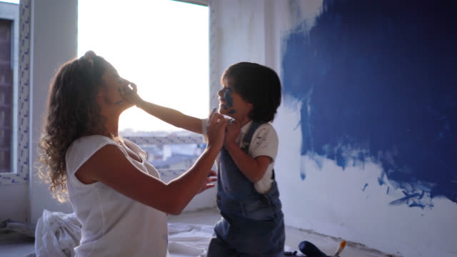 latin american mother and son making a mess very playfully with paint during a home renovation painting their faces - renovation stock videos & royalty-free footage