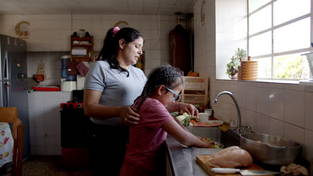 vídeos de stock e filmes b-roll de latin american mother teaching her daughter to cook dinner at home - latin american and hispanic ethnicity