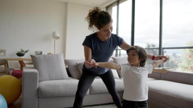 madre latinoamericana che insegna yoga a suo figlio a casa durante il lockdown - son video stock e b–roll