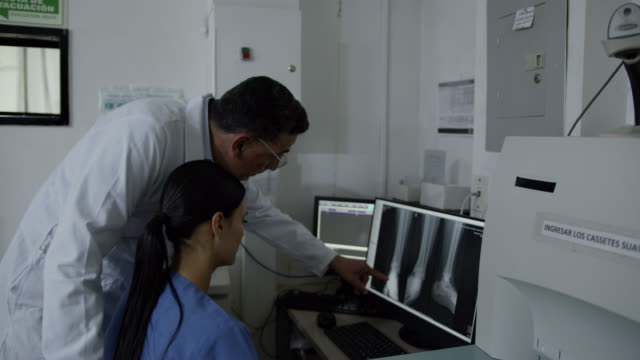 latin american orthopedist and radiologist looking at a patient's xray on screen while discussing - x ray equipment stock videos & royalty-free footage