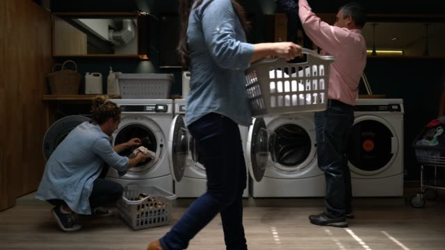 latin american people at a laundry service loading washing machines and walking to one place to another - launderette stock videos & royalty-free footage