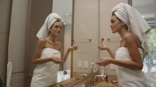 stockvideo's en b-roll-footage met latijns-amerikaanse mooie vrouw die make-up tijdens haar ochtendroutine toepast - in een handdoek gewikkeld