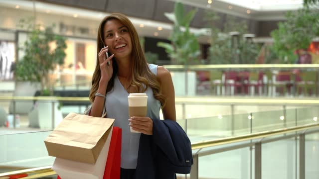 Latin American pretty woman at the mall enjoying a coffee while receiving a phone call very excited and smiling