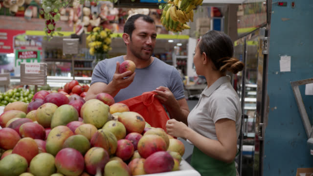 latin american saleswoman at a farmer's market helping customer choose mangoes while he adds them to a reusable bag - local produce stock videos & royalty-free footage