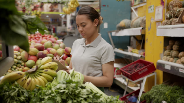 lateinamerikanische verkäuferin, die gemüse an ihrem marktstand mit einer zwischenablage inventarisiert - protective workwear stock-videos und b-roll-filmmaterial