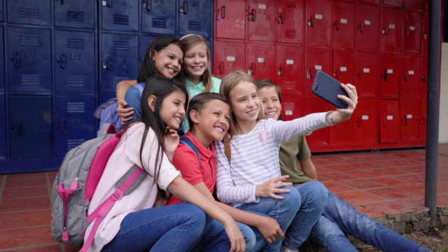 latin american school friends during their break time at school taking a selfie with smartphone - first day of school stock videos & royalty-free footage