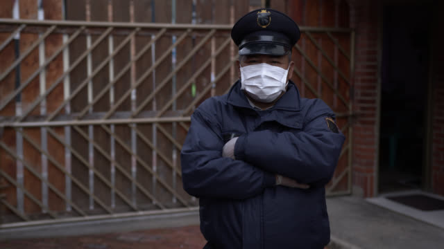 vídeos de stock e filmes b-roll de latin american security guard wearing a protective facemask and gloves facing camera while crossing arms - força policial