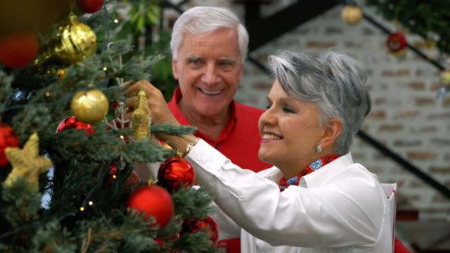 vidéos et rushes de couples aînés latino-américains décorant leur arbre de noel au sourire à la maison - décoration de noël