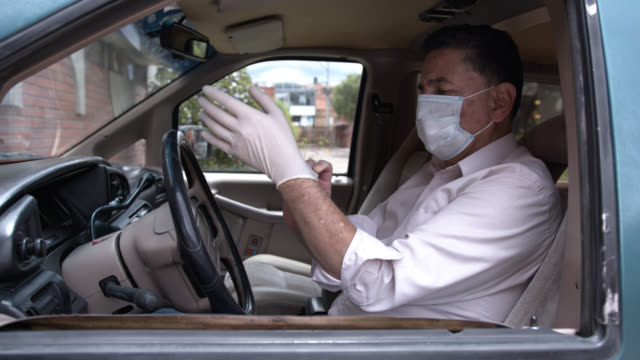 latin american senior man getting ready to drive his car wearing protective face mask and putting on protective gloves - chauffeur stock videos & royalty-free footage