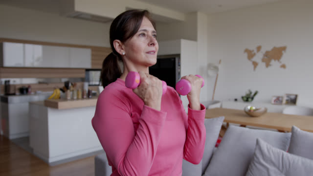 latin american senior woman at home exercising looking focused - exercising stock videos & royalty-free footage