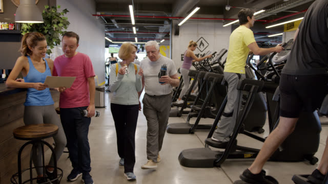 latin american seniors talking and eating while walking at the gym after working out - leisure facilities stock videos & royalty-free footage