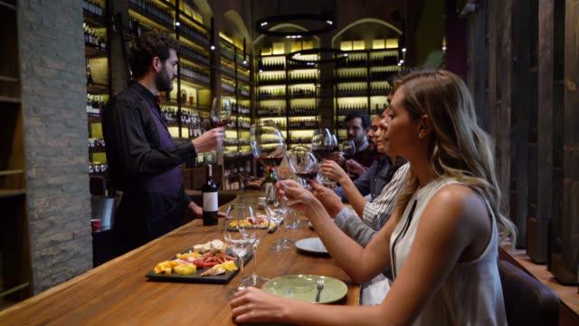 ラテンアメリカのソムリエは、ガラスの質感を見ながらワインについて人々のグループを教えます - ワインバー点の映像素材/bロール