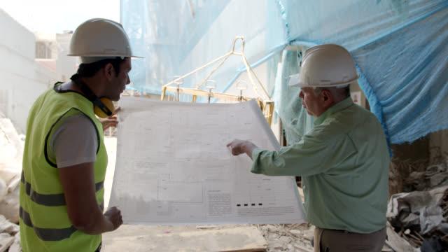 話しながら青写真をチェックする建設現場のラテンアメリカのスーパーバイザーと建築家 - 土木技師点の映像素材/bロール
