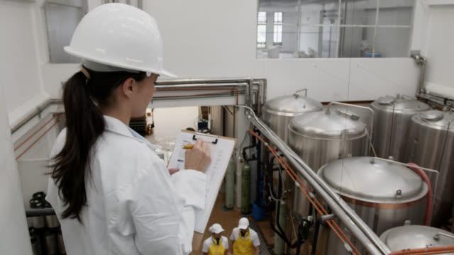 クリップボードにメモを取る生産を監督する醸造所工場のラテンアメリカのスーパーバイザー - 貯蔵タンク点の映像素材/bロール