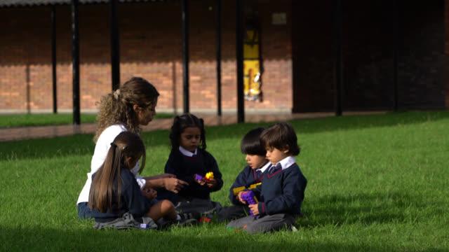 vídeos y material grabado en eventos de stock de profesores latinoamericanos y jóvenes estudiantes jugando con bloques de construcción en el patio de la escuela - uniforme