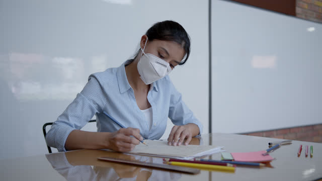 latin american teacher correcting homework from her students wearing a protective face mask - adjusting stock videos & royalty-free footage