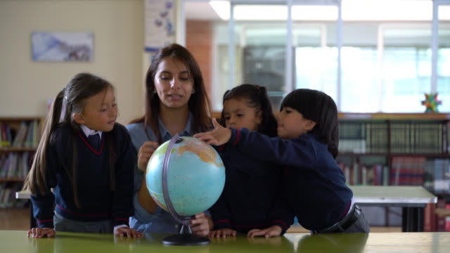 latin american teacher explaining something while pointing at the globe and students paying attention - geografia fisica video stock e b–roll
