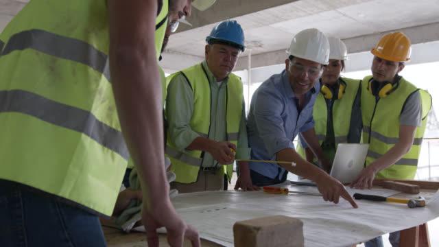 青写真を見ながら、テーブルの周りにプロジェクトを議論する請負業者のラテンアメリカのチーム - 土木技師点の映像素材/bロール