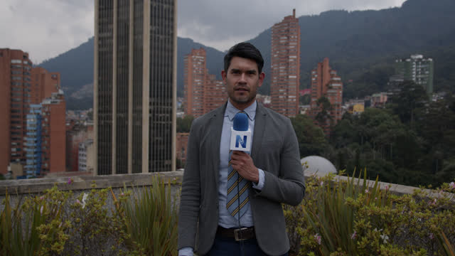 latin american tv reporter outdoors reporting breaking news and looking at the camera while pointing away - documentary footage stock videos & royalty-free footage