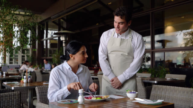 latin american waiter of a luxury hotel approaching female customer enjoying her meal to offer her something - guest stock videos & royalty-free footage