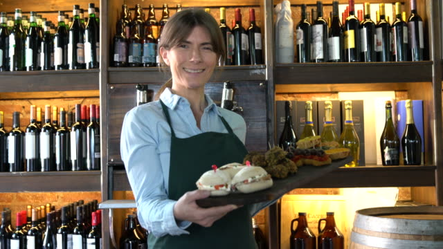 latin american waitress at a wine bar holding a tray with tapas smiling - wine bar stock videos & royalty-free footage
