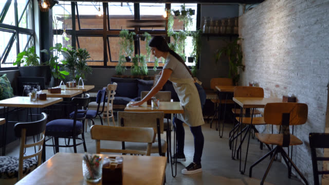 latin american waitress organizing and cleaning the tables at a restaurant - clean stock videos & royalty-free footage
