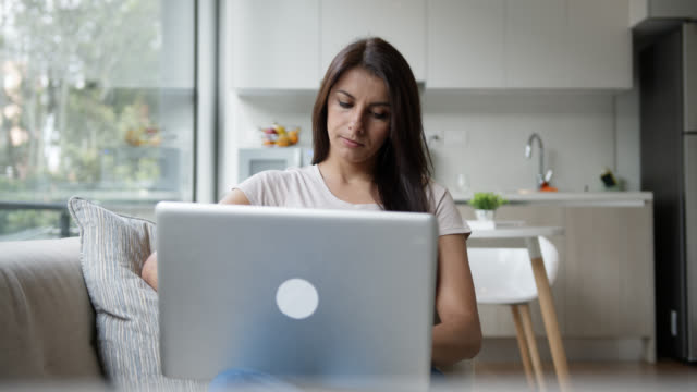 vídeos de stock e filmes b-roll de latin american woman at home browsing online on her laptop computer while lying on the couch - latin american and hispanic ethnicity