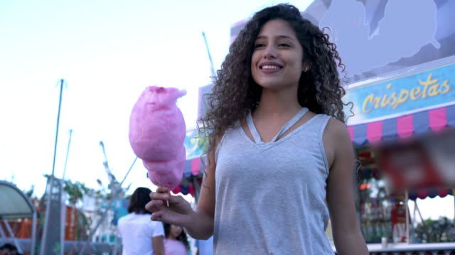 Latin American woman eating a cotton candy while walking around an amusement park looking very happy