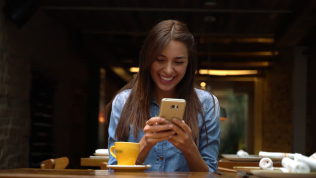 Latin american woman enjoying a coffee and chatting on her phone laughing