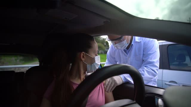 vídeos de stock e filmes b-roll de latin american woman getting the covid-19 vaccine at a drive through center while doctor talks to her - latin american and hispanic ethnicity