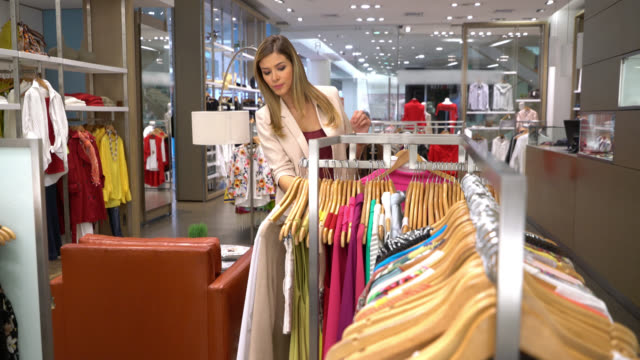latin american woman looking at clothes hanging on retail display - garment stock videos & royalty-free footage