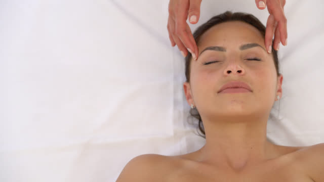 latin american woman receiving a head massage at a spa - head massage stock videos and b-roll footage