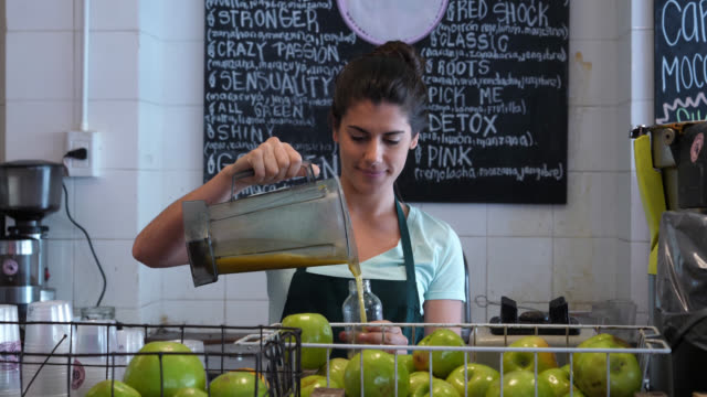 Latin american woman working at a juice bar using the blender and then serving the juice in a bottle