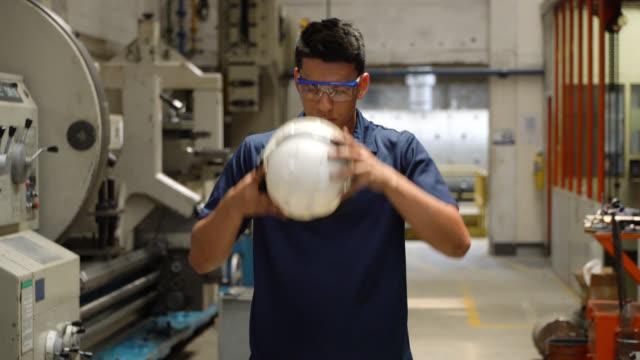 vídeos y material grabado en eventos de stock de trabajador latinoamericano en una fábrica de metalurgia que lleva ropa de trabajo protectora - guantes de protección