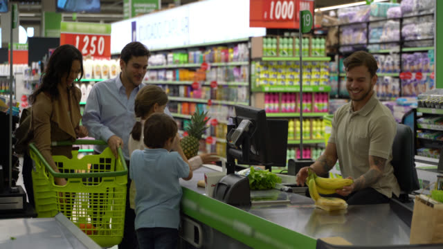 latin american young beautiful family at the supermarket's checkout and the kids handing groceries to male cashier - megastore stock videos & royalty-free footage