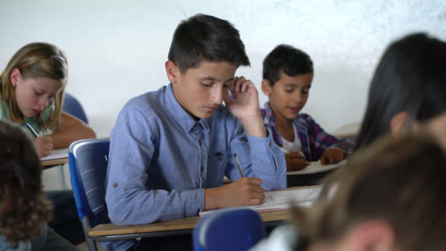 latin american young male student working very focused on his notebook during class - junior high stock videos & royalty-free footage