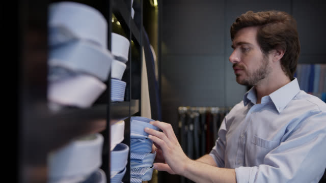 latin american young man choosing a button down shirt from a shelve at a men's clothing store - tailored clothing stock videos & royalty-free footage
