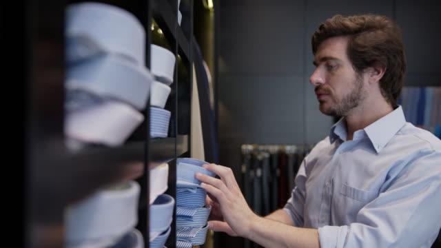 lateinamerikanische junge mann wahl ein button-down-shirt aus einem regal in einem herren-kleidungsgeschäft - maßkonfektion stock-videos und b-roll-filmmaterial