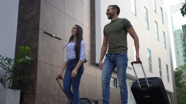 latin american young tourists walking towards the hotel each pulling their wheeled luggage both smiling - wheeled luggage stock videos & royalty-free footage