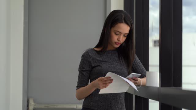 電話でテキストメッセージを送りながら文書を見ているコワーキングオフィスのラテンアメリカの若い女性 - casual clothing点の映像素材/bロール