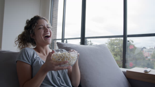latin american young woman at home watching a funny movie laughing while eating pop corn during pandemic lockdown - mental wellbeing stock videos & royalty-free footage