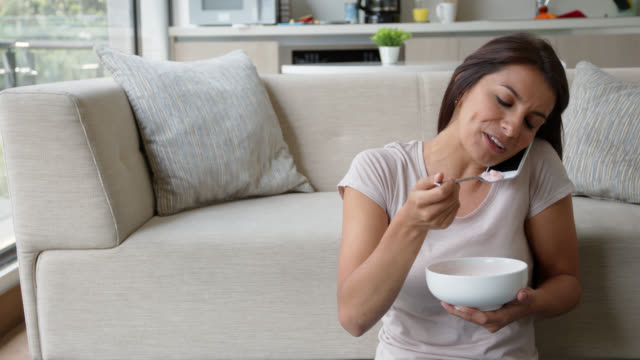 latin american young woman on a phone call while enjoying a bowl of fruits and cereal at home - stereotypical homemaker stock videos & royalty-free footage