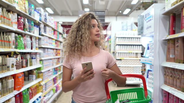 latin american young woman shopping at the supermarket carrying a basket and looking at shopping list on smartphone - hygiene stock videos & royalty-free footage