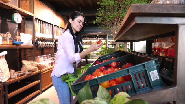 latin american young woman shopping for groceries at an organic store smelling and choosing tomatoes while putting them in a basket - cereal plant stock videos & royalty-free footage