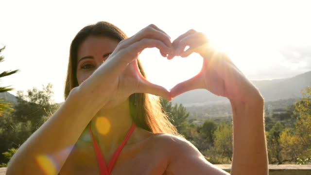 Latin American/Hispanic girl making heart shape with hands to camera.