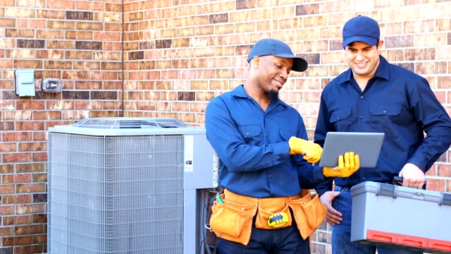 latin and african american blue collar workers fixing ac unit in backyard - tecnico video stock e b–roll