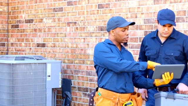 latin and african american blue collar workers fixing ac unit in backyard - repairman stock videos & royalty-free footage